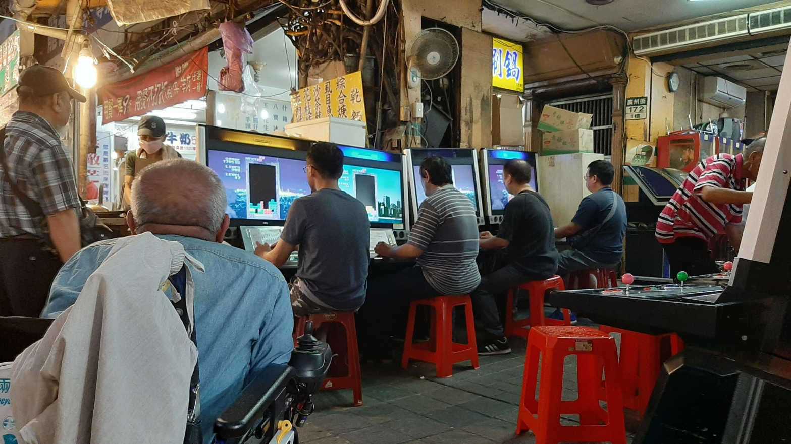 Several men at a Taiwanese night market playing Tetris on large computers.